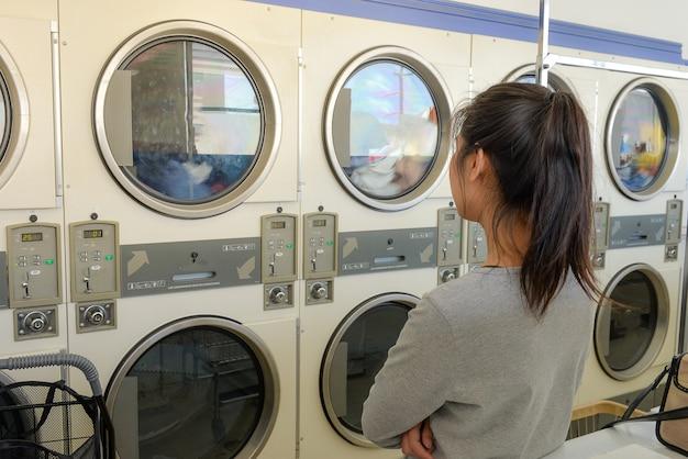 Macchina di lavanderia aspettante della donna asiatica in lavanderia pubblica pubblica.