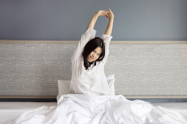 La donna asiatica si sveglia e allunga il braccio sul letto la mattina