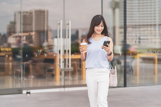Donna asiatica che cammina in città e usa il telefono cellulare e tiene in mano una tazza di caffè di carta
