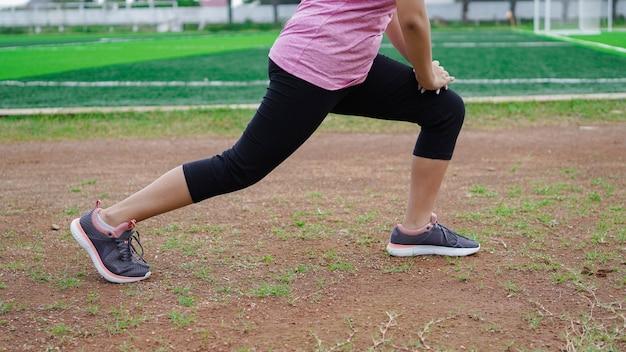 Donna asiatica in fase di riscaldamento prima di correre. chiudere le gambe
