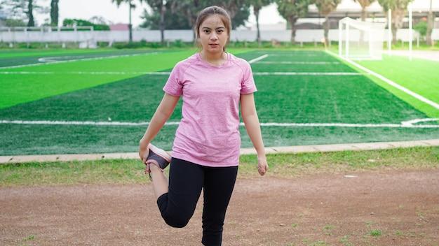 Donna asiatica in fase di riscaldamento prima di correre
