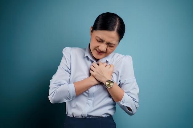 La donna asiatica era malata di dolore al petto in piedi isolato sul blu.
