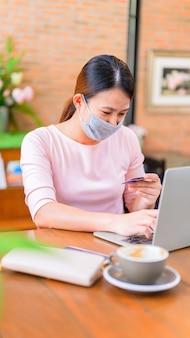 La donna asiatica indossa la maschera per il viso e lo shopping online. distanziamento sociale e nuovo stile di vita normale.