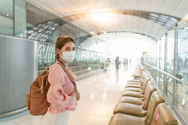 La donna asiatica indossa le maschere all'aeroporto