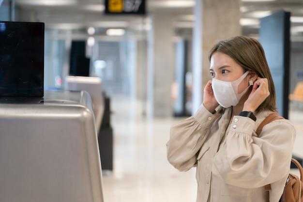 Le donne asiatiche indossano maschere mentre viaggiano al banco del check-in dei clienti della compagnia aerea nuova normale prevenzione delle malattie covid