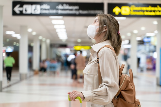 La donna asiatica indossa maschere mentre viaggia al terminal dell'aeroporto nuovo normale covid