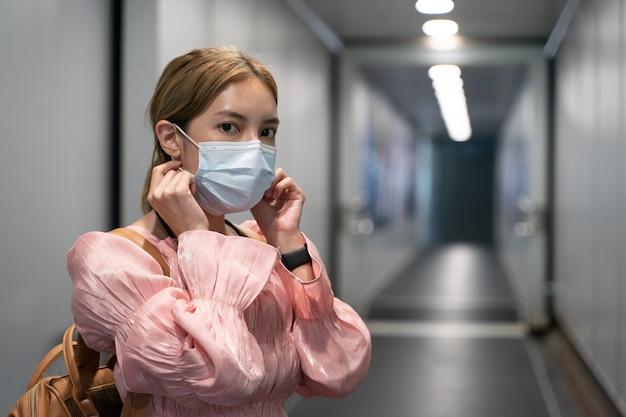 La donna asiatica indossa maschere mentre viaggia al terminal dell'aeroporto new normal