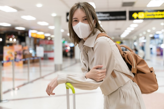 La donna asiatica indossa maschere mentre viaggia al terminal dell'aeroporto
