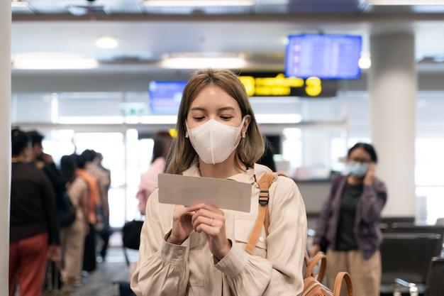 La donna asiatica indossa maschere mentre viaggia tenendo la carta d'imbarco al terminal dell'aeroporto nuovo normale