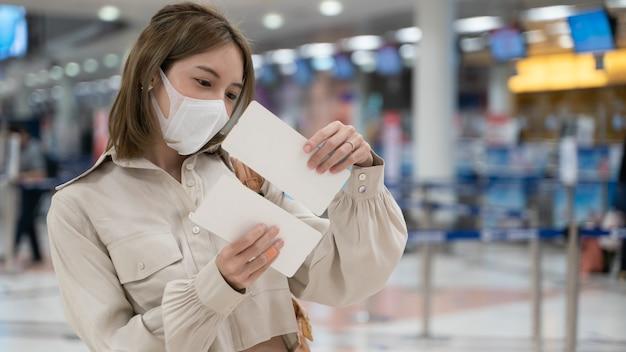 La donna asiatica indossa maschere durante il viaggio, tenendo la carta d'imbarco al terminal dell'aeroporto
