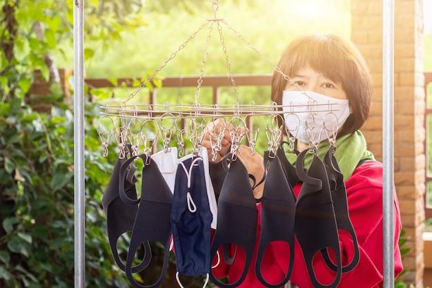 La maschera chirurgica di usura della donna asiatica viene lavata e asciugata le maschere per il riutilizzo di anti batteri e virus per creare una nuova maschera