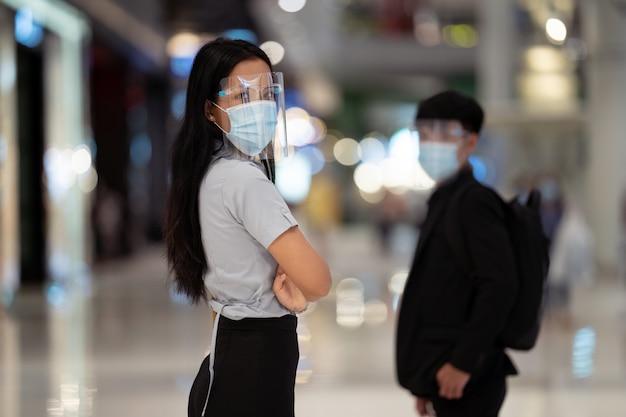 La donna asiatica indossa una maschera di protezione antivirus. nel centro commerciale