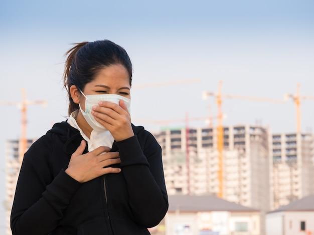 Donna asiatica che indossa una maschera facciale e tossisce a causa dell'inquinamento