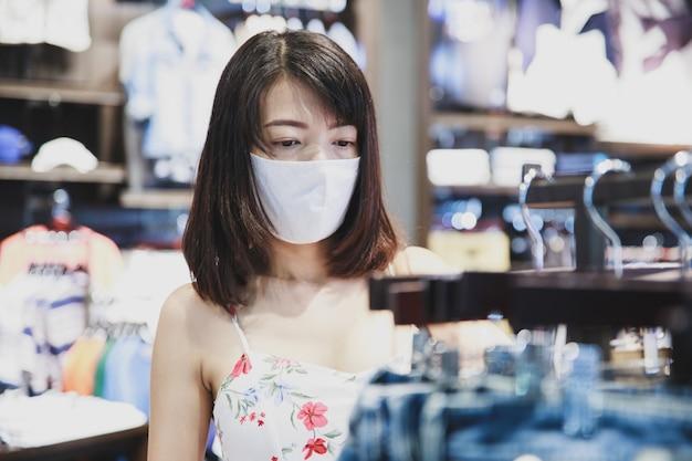 Donna asiatica che indossa una maschera in un posto per lo shopping