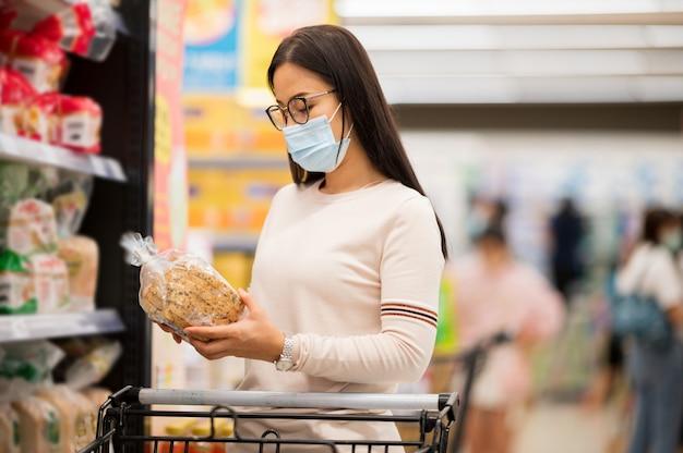 Acquisto da portare della maschera di protezione della donna asiatica nel supermaket durante il virus della corona