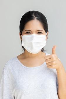 Donna asiatica che indossa la maschera per il viso pollice in su