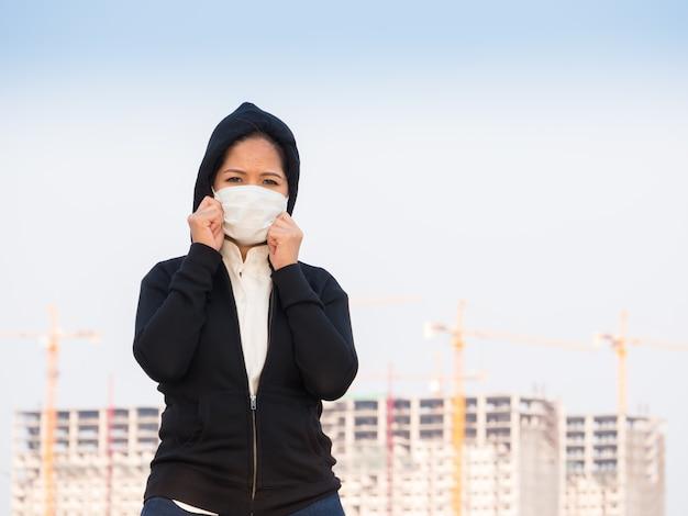Donna asiatica che indossa una maschera facciale con sfondo di costruzione