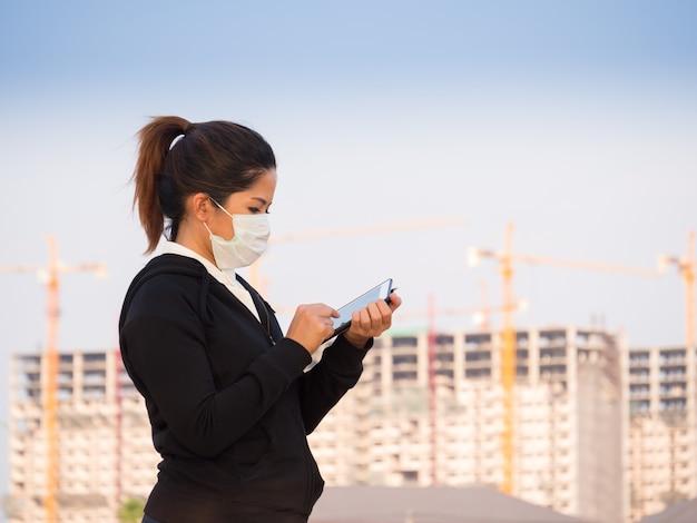 Donna asiatica che indossa una maschera facciale e lavora con sfondo di costruzione