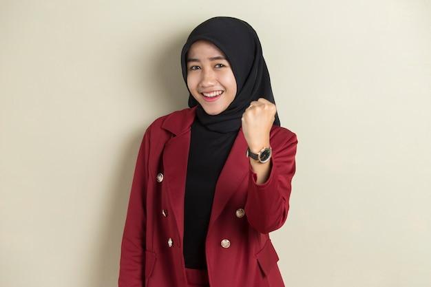 Donna asiatica che indossa l'hijab felice ed emozionata che celebra la vittoria che esprime grande successo, potenza, energia ed emozioni positive. celebra il nuovo lavoro con gioia