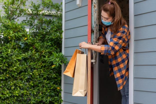 Donna asiatica che indossa una maschera ha ricevuto l'oggetto consegnato alla porta d'ingresso del servizio coronavirus pandemico in quarantena del servizio di concetto di casa [covid-19]. resta a casa, nuovo normale