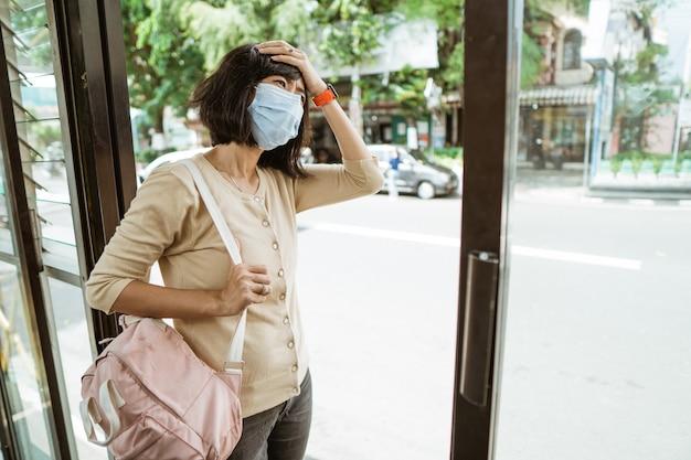 Una donna asiatica che indossa una maschera sta aspettando l'autobus alla fermata dell'autobus in una giornata calda