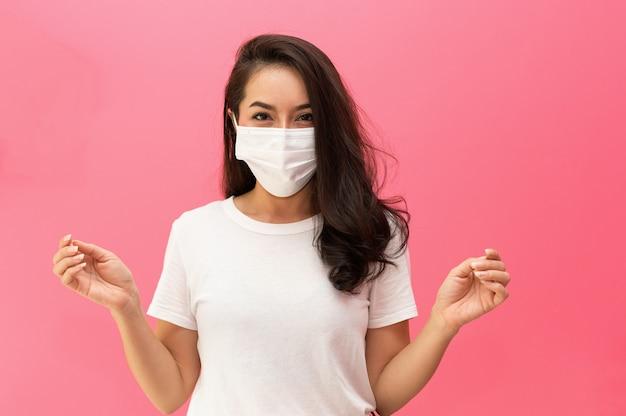 Donna asiatica che indossa maschera facciale medica sulla parete rosa