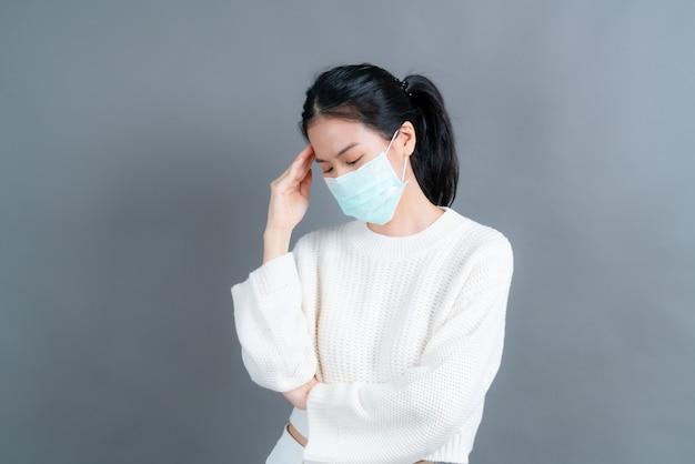 La donna asiatica che indossa una maschera medica protegge la polvere del filtro pm2.5 anti-inquinamento, anti-smog e covid-19 e ha mal di testa sul muro grigio