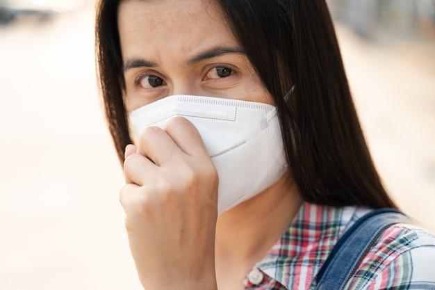 Donna asiatica che indossa la maschera facciale n95 per proteggere l'inquinamento pm2.5 e virus. covid-19 coronavirus e inquinamento atmosferico pm2.5 concetto sanitario e medico.
