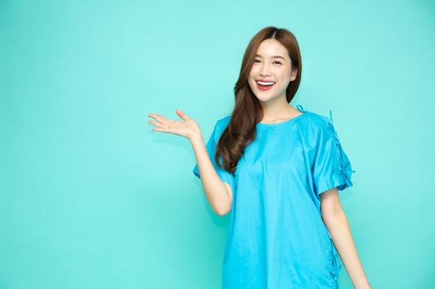 Donna asiatica indossando abiti paziente che presenta o mostra palmo della mano aperta con copia spazio per il prodotto isolato su sfondo verde