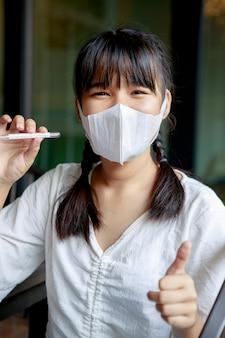 Donna asiatica che indossa la maschera di protezione