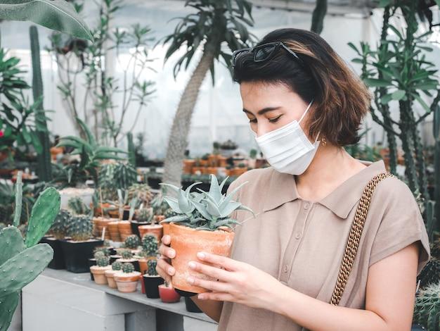 Donna asiatica che indossa una maschera protettiva cercando piccolo cactus in vaso di terracotta