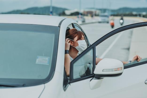 Donna asiatica che indossa una maschera protettiva per la protezione della protezione prima di uscire dall'auto durante la pandemia di coprifuoco all'aperto del coronavirus covid-19
