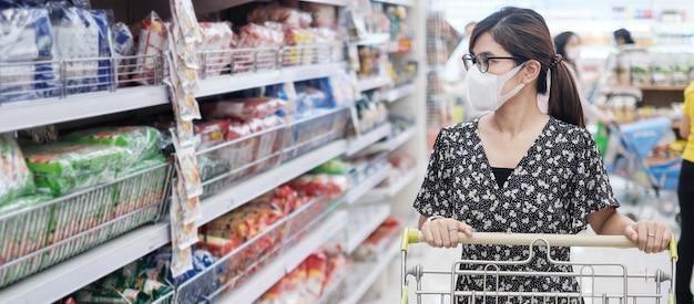 La donna asiatica che indossa la maschera protettiva e che compera nel supermercato o nella drogheria, protegge l'inflessione del coronavirus. distanza sociale, nuova normalità e vita dopo la pandemia covida-19