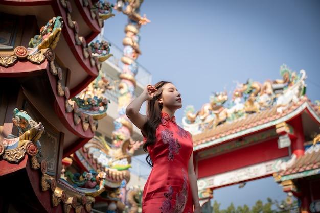 Donna asiatica che indossa un abito rosso cheongsam al santuario cinese. anno nuovo cinese concetto.
