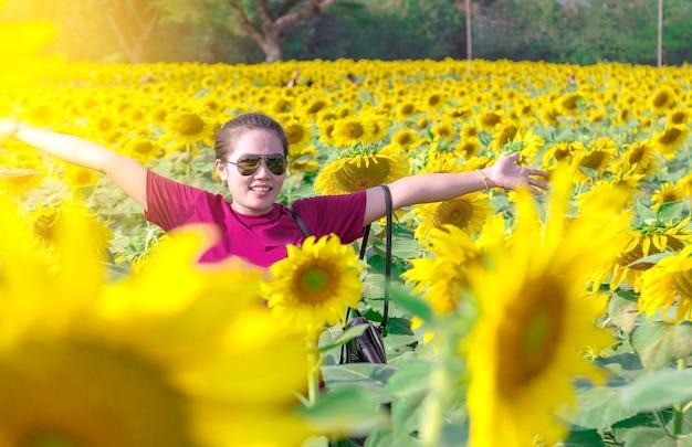 Donna asiatica che indossa occhiali da sole in piedi pone in mezzo ai campi di girasole.