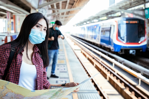 Donna asiatica che indossa una maschera chirurgica contro il nuovo coronavirus o malattia da virus corona covid e legge la mappa di viaggio alla stazione ferroviaria pubblica rilassati e trova la posizione sullo sky train