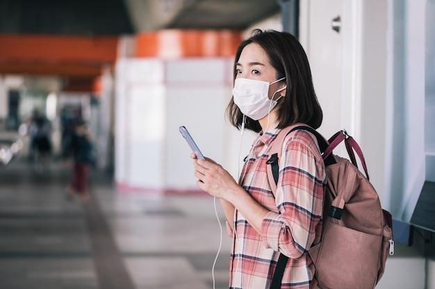Donna asiatica che indossa una maschera chirurgica contro il nuovo coronavirus o malattia da coronavirus alla stazione ferroviaria pubblica Foto Premium