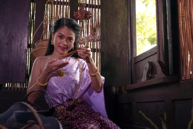 Donna asiatica che indossa il costume tailandese del vestito tradizionale secondo la cultura e la tradizione che cucinano nella cucina alla casa antica ayutthaya, tailandia