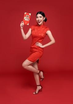 Donna asiatica che indossa abito tradizionale qipao cheongsam che tiene angpao o regalo monetario pacchetto rosso isolato sulla parete rossa.