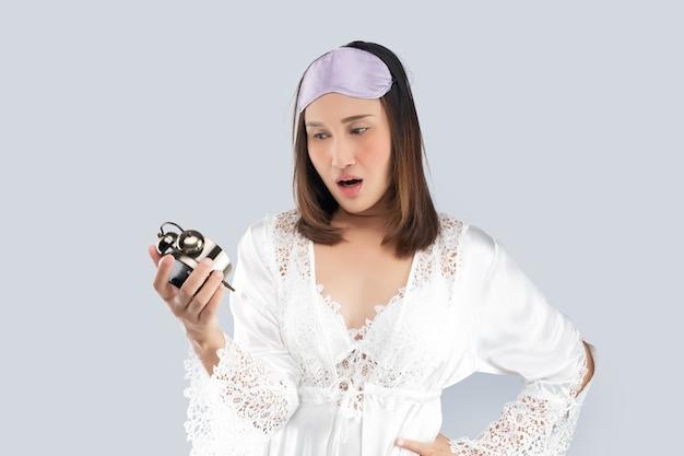 Una donna asiatica in camicia da notte di raso bianco e vestaglia di pizzo è scioccata mentre si sveglia tardi. una ragazza che si sveglia tardi guarda la sveglia su uno sfondo grigio chiaro.