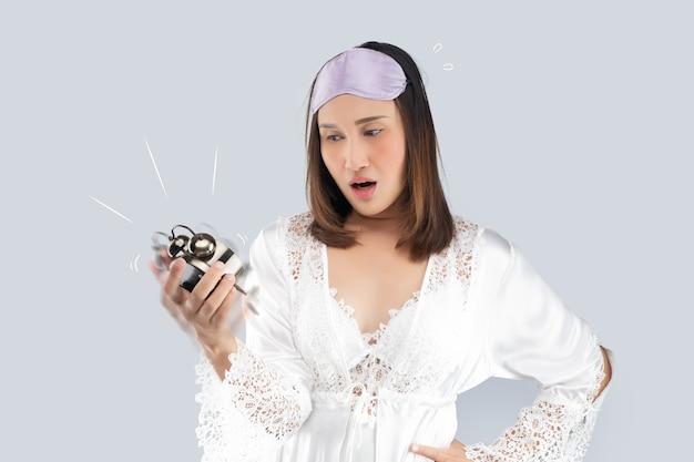 Donna asiatica in una camicia da notte di raso bianco e vestaglia di pizzo scioccata mentre si sveglia tardi.