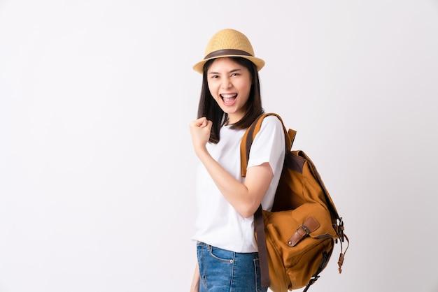 La donna asiatica in una maglietta bianca e porta uno zaino con i pugni chiusi