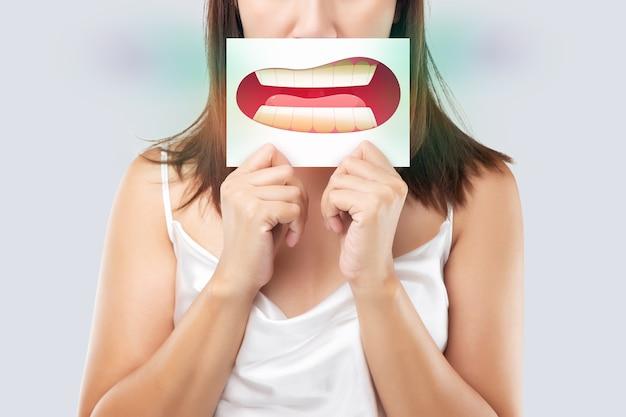 Donna asiatica nell'abbigliamento bianco che tiene una carta bianca con l'immagine del fumetto dei denti gialli della sua bocca sullo sfondo grigio, alitosi o alitosi, il concetto con gengive e denti sanitari