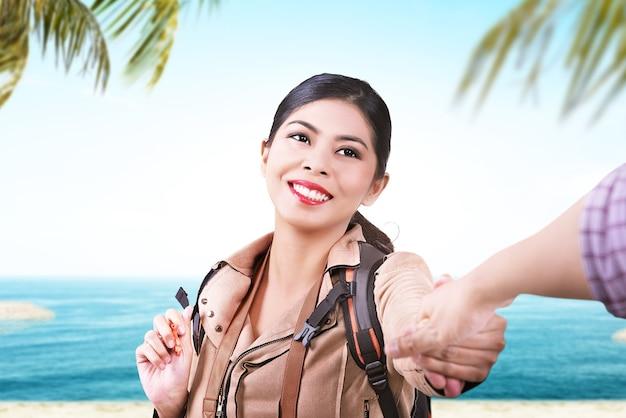 Donna asiatica con uno zaino che tiene la mano del suo ragazzo mentre viaggia sulla spiaggia con lo sfondo del cielo blu