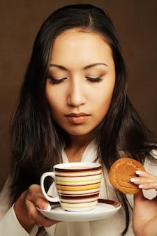 Donna asiatica con caffè e biscotti.
