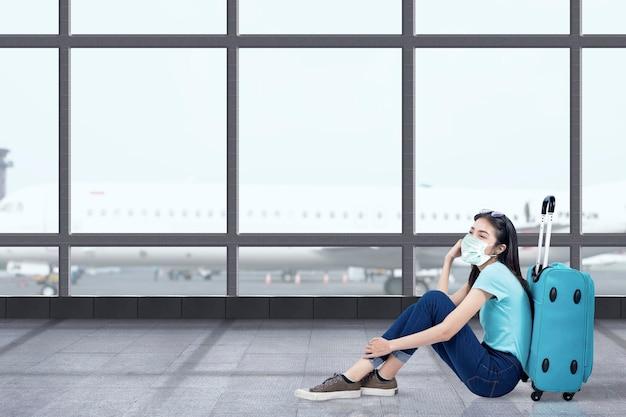 Donna asiatica con una maschera per il viso seduto con una valigia al terminal dell'aeroporto. viaggiare nella nuova normalità