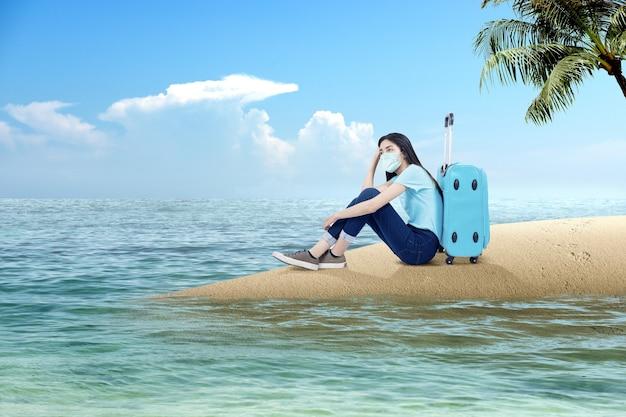 Donna asiatica con una maschera per il viso seduta con una valigia sulla spiaggia