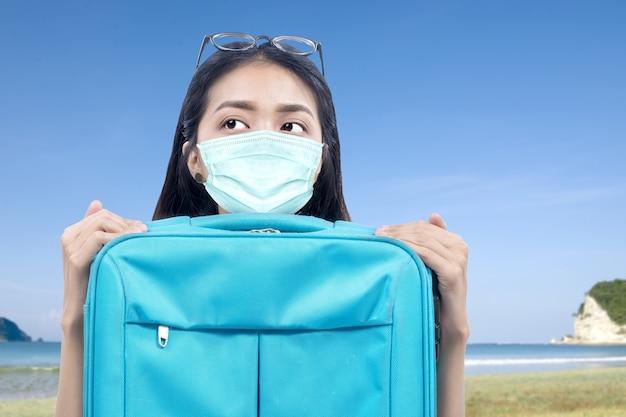 Donna asiatica con una maschera per il viso con una valigia sulla spiaggia. viaggiare nella nuova normalità