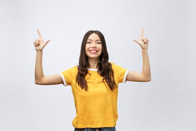 Donna asiatica con il dito puntato verso l'alto isolare su bianco