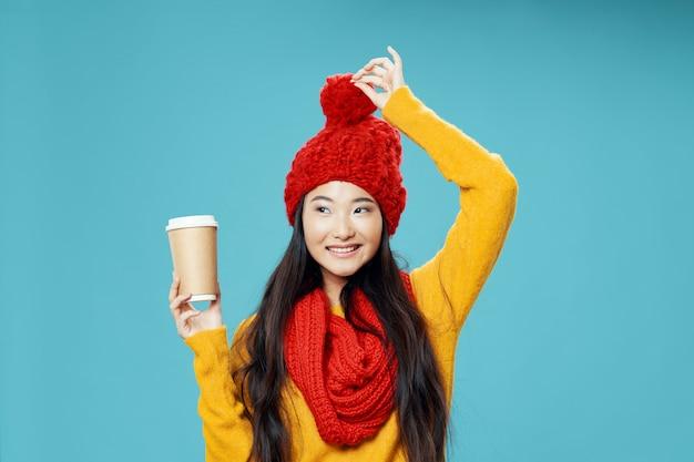 Donna asiatica con soffice cappello e tazza di caffè